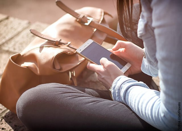 Foto de una mujer manipulando su celular
