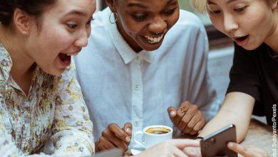 Foto de tres mujer divirtiéndose mientras miran su celular
