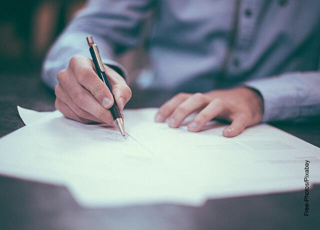 Foto de un hombre escribiendo sobre un papel