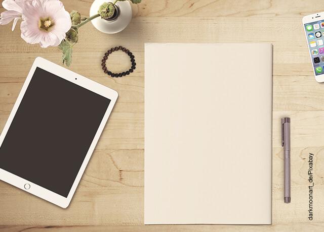 Foto de una tablet encima de una mesa de madera