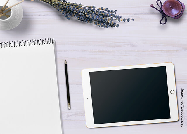 Foto de una tablet junto con una libreta sobre una mesa