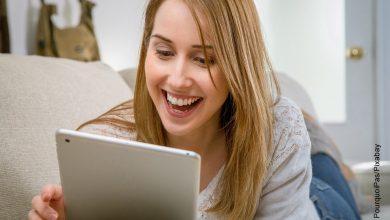 Foto de una mujer sonriendo frente a una tablet que ilustra cómo hacer una carta de petición