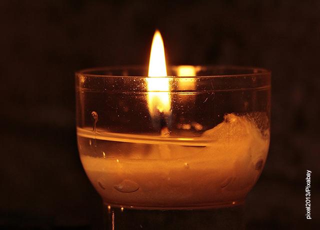 Foto de una vela encendida en un recipiente de vidrio