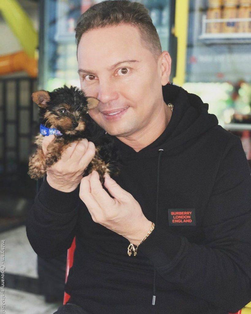 Foto de Giovanny Ayala alzando a su perro pequeño