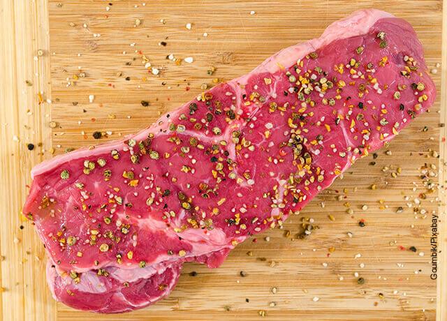 Foto de un trozo de carne con especias sobre una tabla de madera que ilustra cómo hacer costillas bbq con una receta tradicional