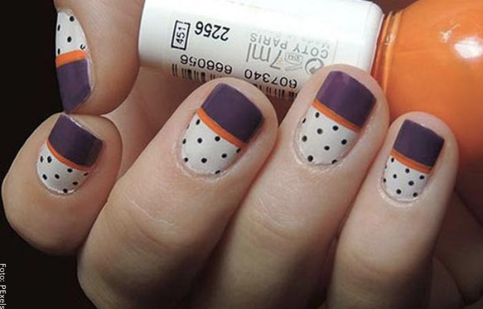 Foto de unas uñas decoradas con diseño mitad puntos, mitad tono neutro