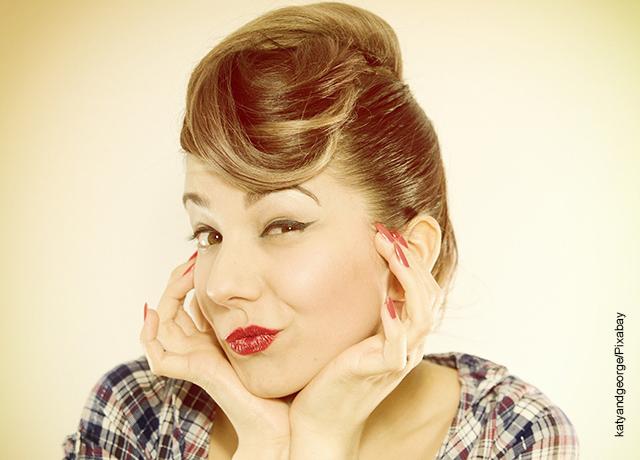 Foto de una mujer pin up tomándose el rostro y lanzando un beso