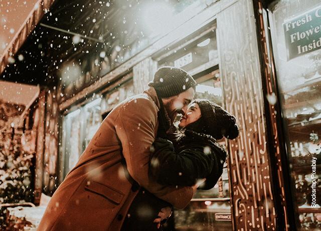 Foto de una pareja besándose bajo la nieve que ilustra las frases de películas de amor