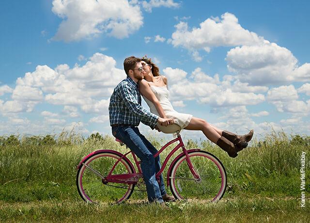 Foto de una pareja montando bicicleta por el campo