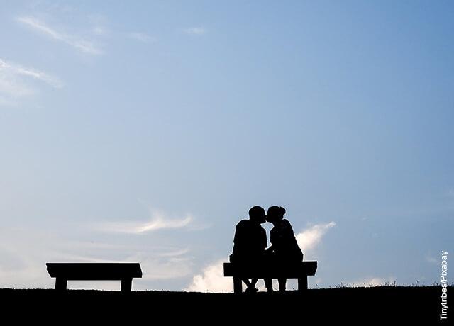 Foto de una pareja de novios besándose en una banca de un parque
