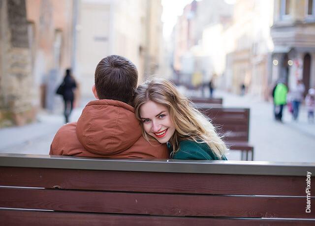 Foto de una pareja de novios sentados en una banca sonriendo