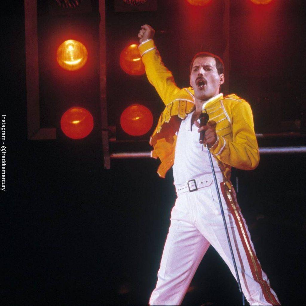 Foto de Freddie Mercury durante un concierto con su chamarra amarilla