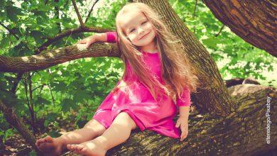 Foto de una niña sonriendo encima de una rama de árbol que ilustra los nombres de niña