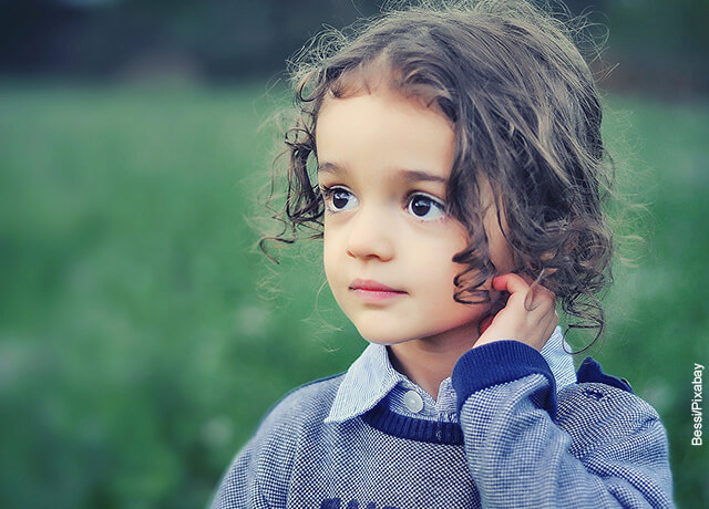 Foto de una niña tomándose su pelo rizado