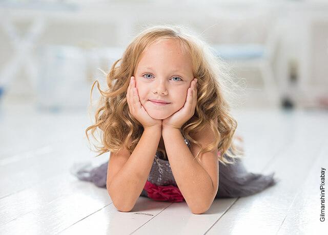 Foto de una niña rubia acostada en el piso