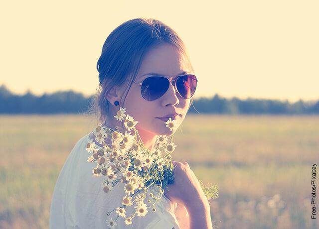 Foto de una mujer al aire libre con unas flores en sus manos que muestra los nombres raros para niñas