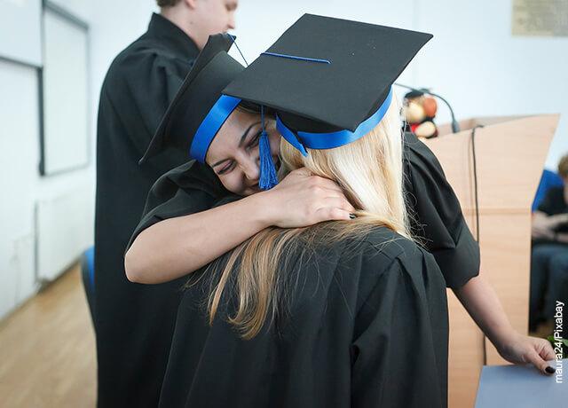 Foto de dos mujeres abrazándose en su grado