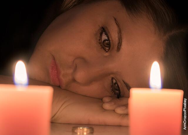 Foto de una mujer triste viendo dos velas prendidas