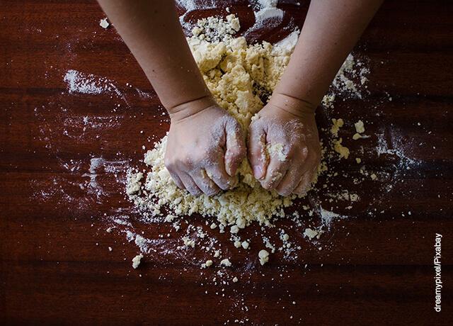 Foto de unas manos amasando sobre una mesa que ilustra el pan de yuca y su receta