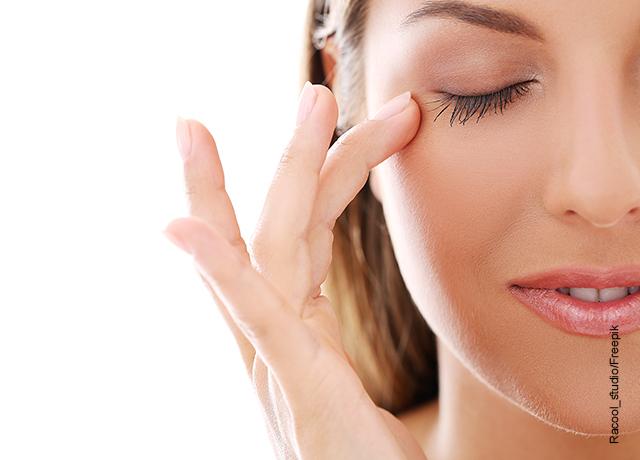 Foto de una mujer aplicando crema sisbre sus ojos