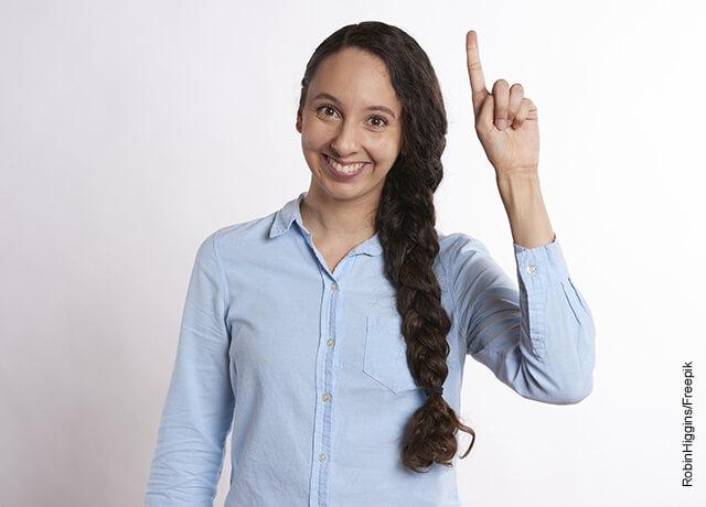 Foto de una mujer levantando su mano para preguntar