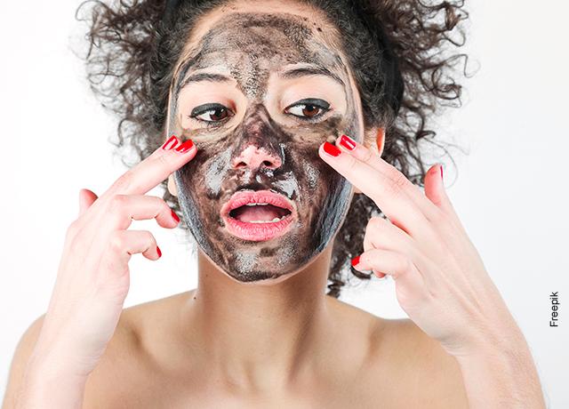 Foto de una mujer aplicándose una mascarilla negra