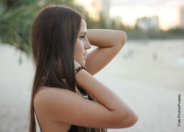 Foto de una mujer tocándose su cabellera