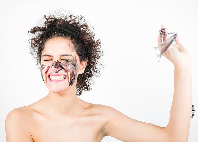Foto de una mujer sonriendo con una mascarilla negra en su rostro