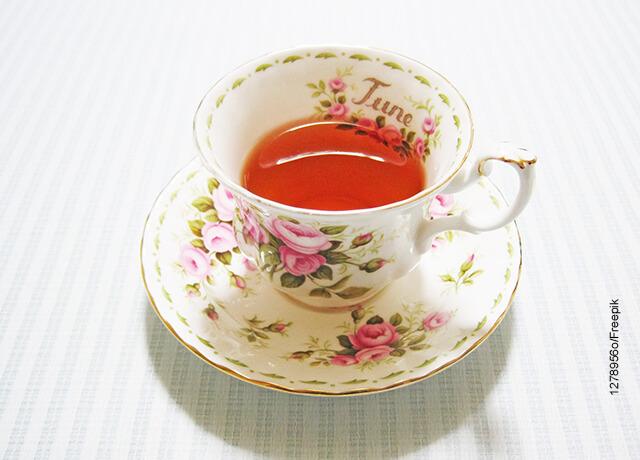 Foto de una taza de té servida en pocillo de flores