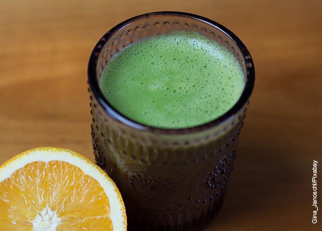 Foto de un batido de jugo verde en un vaso con una naranja