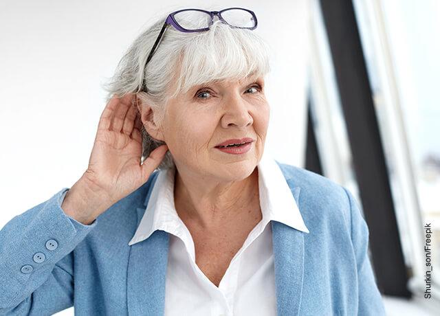 Foto de una mujer de la tercera edad tomándose un oído