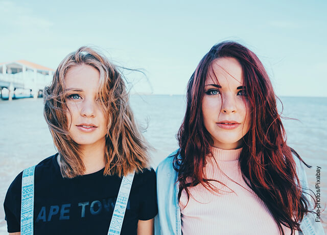 Foto de dos mujeres sonriendo a la cámara en la playa