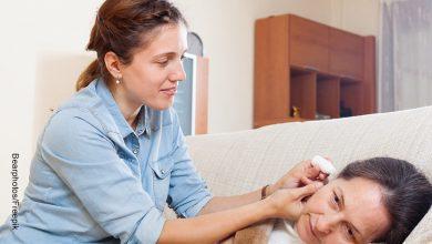 Foto de una mujer aplicándole a otra gotas para el oído que muestra para qué sirve la glicerina carbonatada