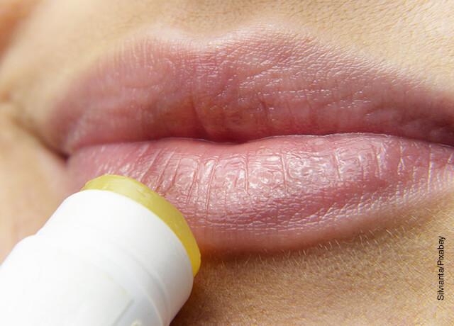 Foto de una mujer aplicándose labial