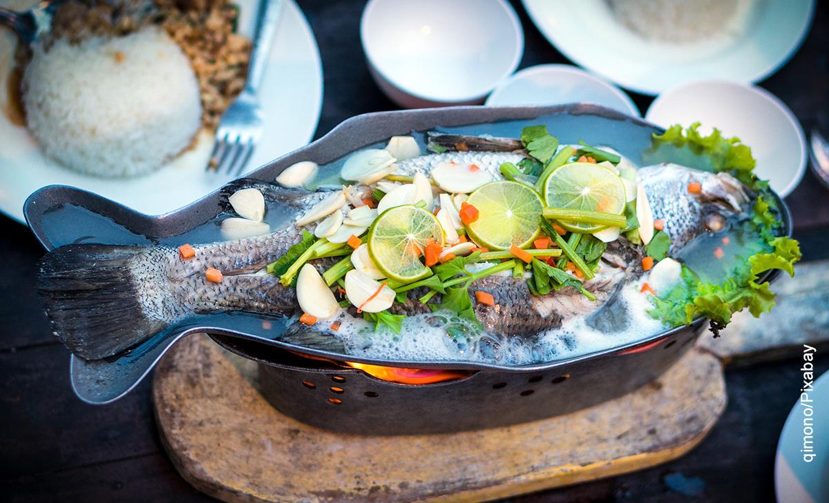 Foto de un pescado guisado con verduras por encima sobre un plato que muestra para qué sirve la proteína