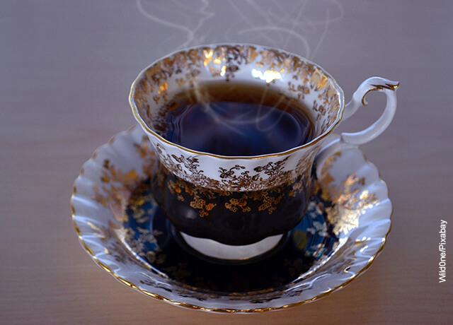 Foto de una taza de té negro servido en una vajilla dorada