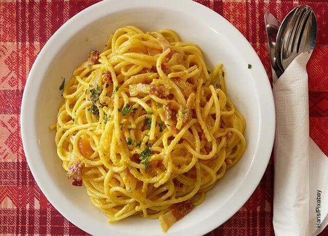 Foto de un plato de espaguetis a la carbonara sobre un mantel rojo