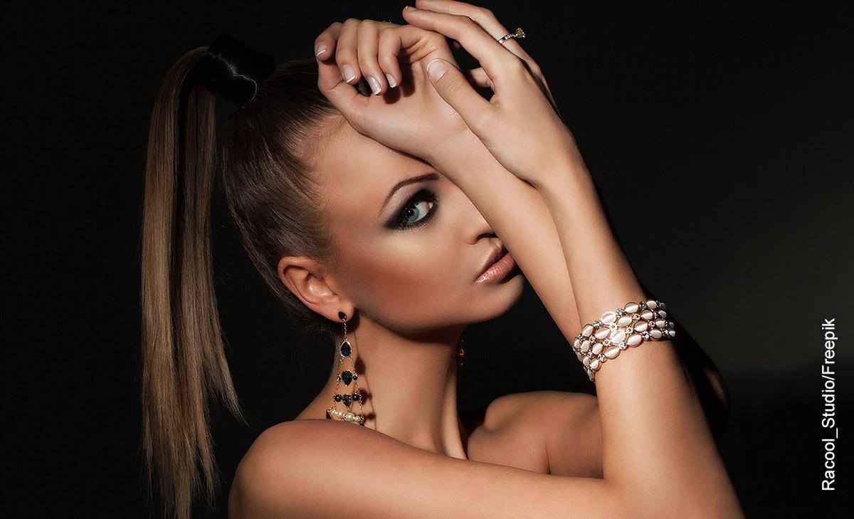 Foto de una modelo luciendo joyas y que revela los peinados con cola alta