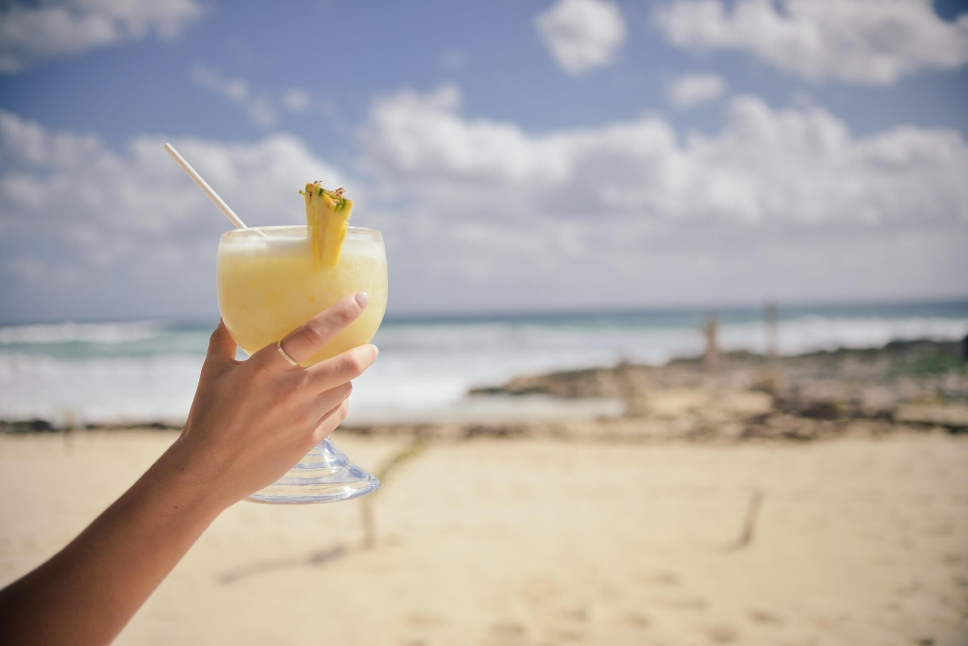 Foto de una mujer sosteniendo un coctel que ilustra una piña colada y su receta
