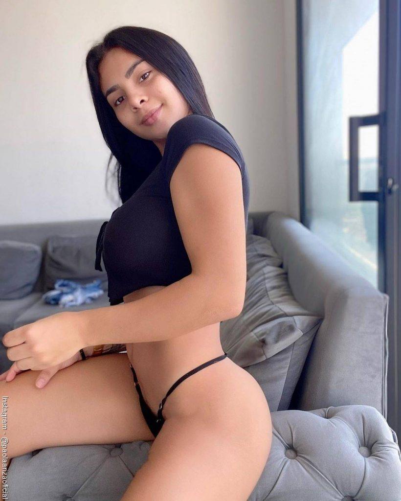 Foto de la modelo Paola Ariza sentada de medio lado en el sofá luciendo una tanga brasilera negra