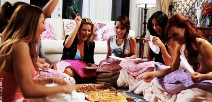 Foto de varias mujeres comiendo pizza para ilustrar qué hacer en una pijamada