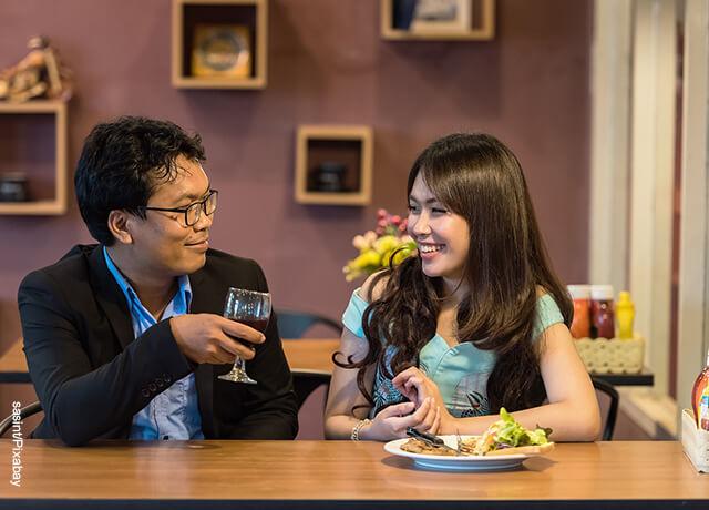 Foto de un hombre y una mujer cenando juntos que ilustra qué preguntarle a una mujer