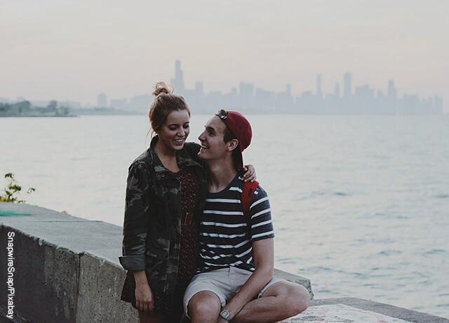 Foto de una pareja joven sentados en un muelle sonriendo