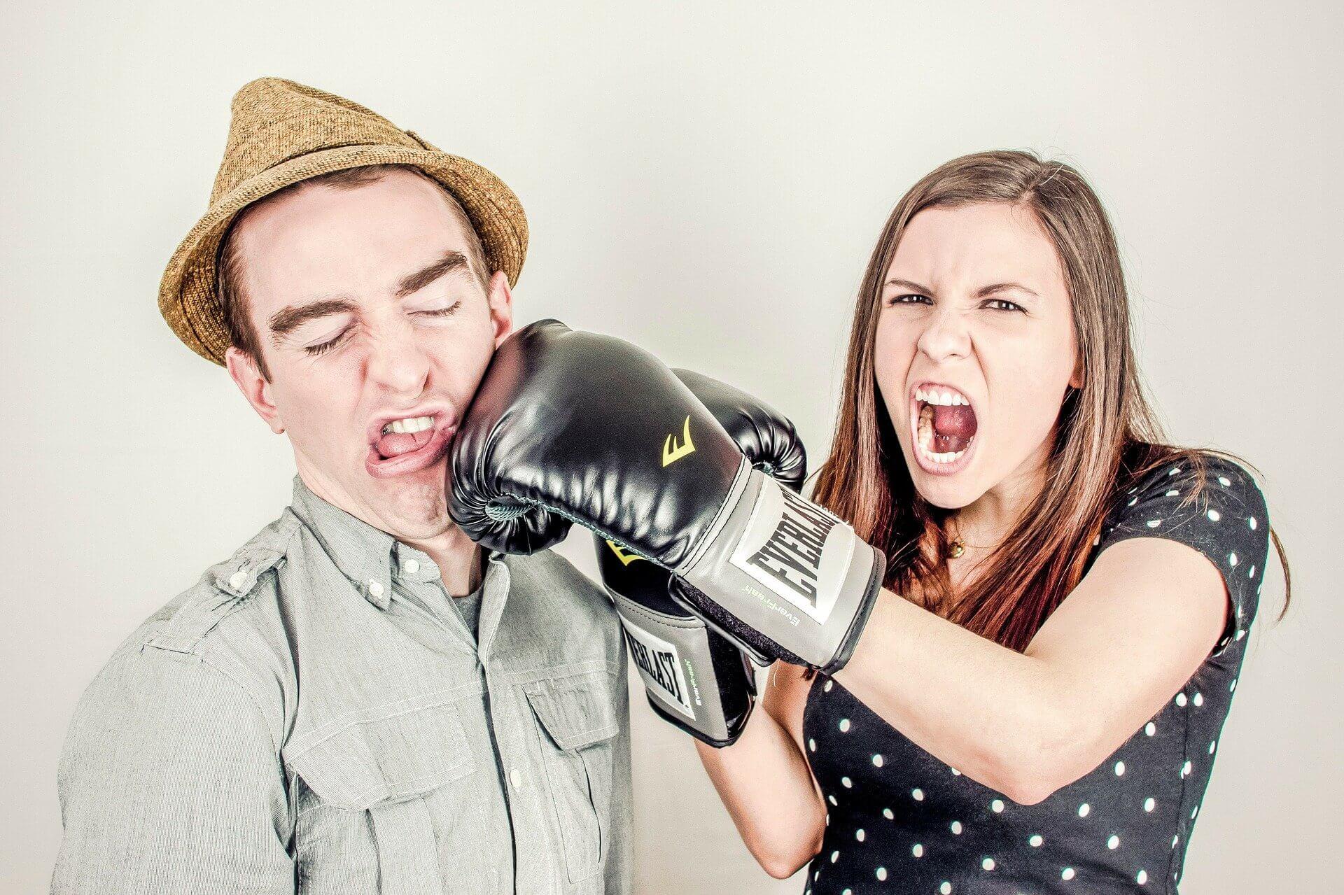 Foto de una mujer con guantes de boxeo golpeando a un hombre