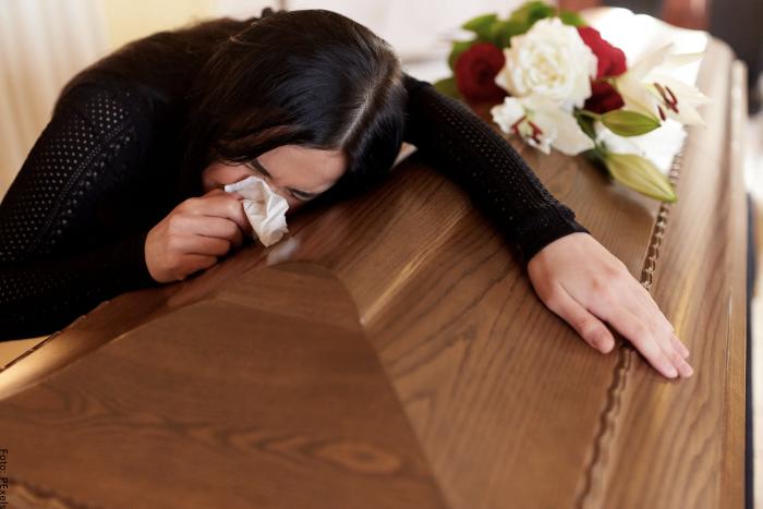 Foto de una mujer llorando sobre un ataud
