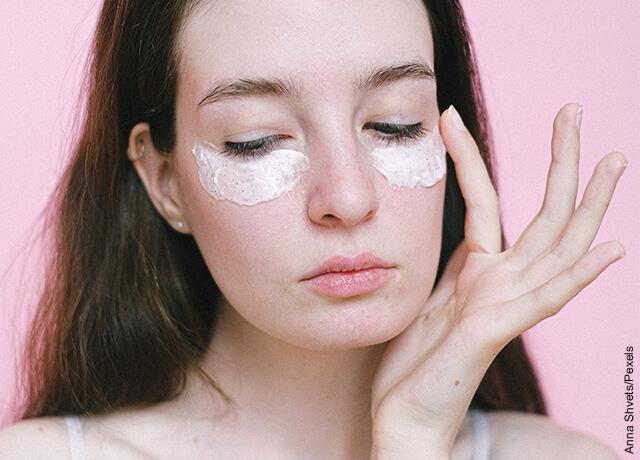 Foto de una mujer joven que aplica en sus párpados una mascarilla