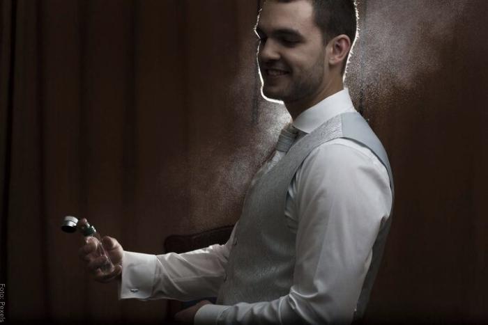 Foto de un hombre aplicándose perfume