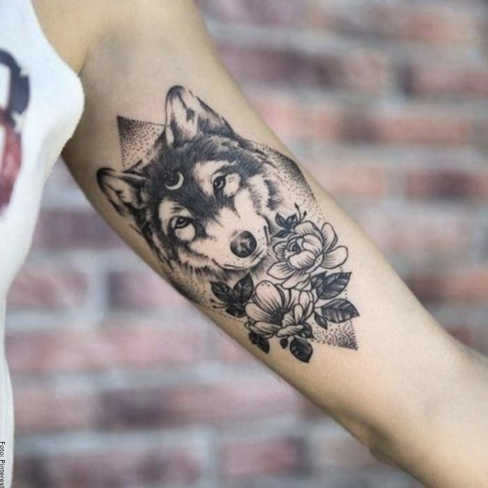 Foto de un tatuaje de un lobo rodeado de rosas