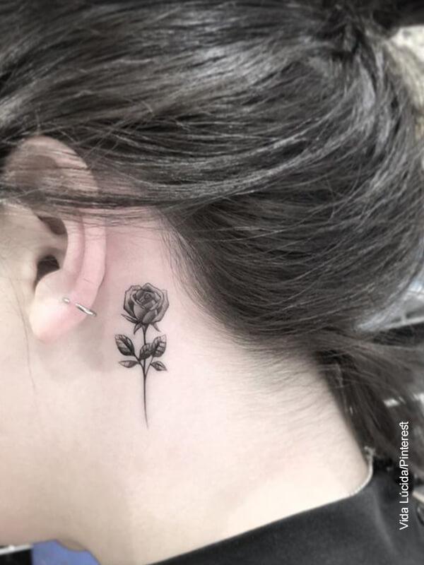 Foto de una mujer con un tatuaje de rosa detrás de su oreja