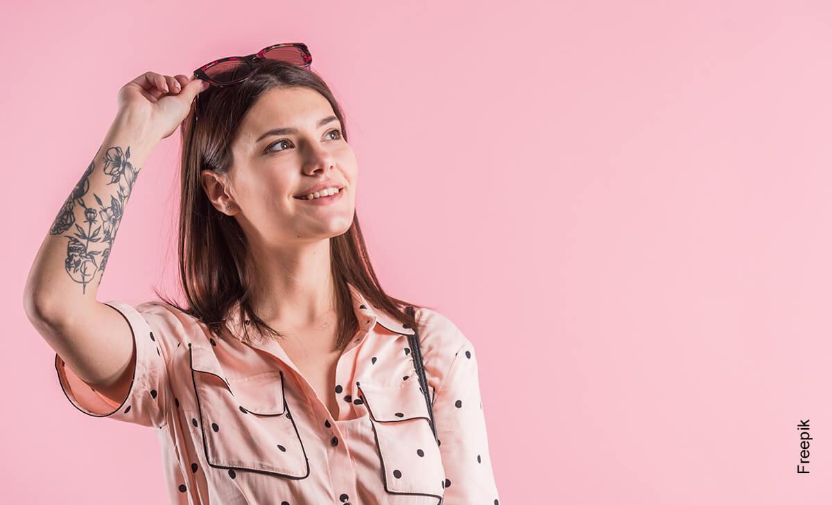 Foto de una mujer joven sonriendo frente a una pared rosada que muestra las rosas en los tatuajes
